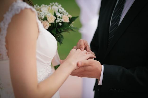 Novio poniendo un anillo de bodas en el dedo de la novia