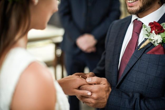 Novio poniéndose el anillo de bodas de su novia