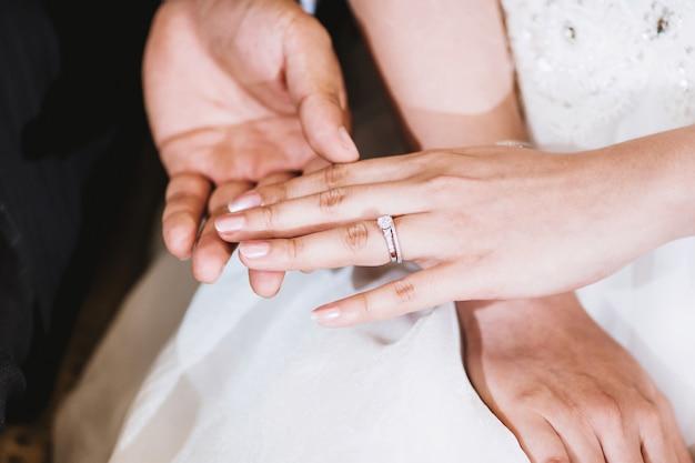 El novio que sostiene la mano de la novia después de poner el anillo de bodas en su dedo