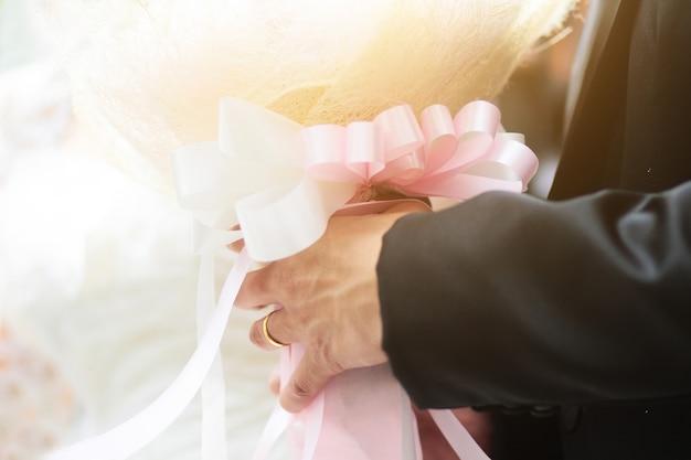 Novio que sostiene el ramo de las flores color de rosa con luz del sol en matrimonio.