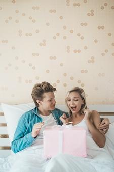 Novio sorprende a su novia con caja de regalo en la cama.