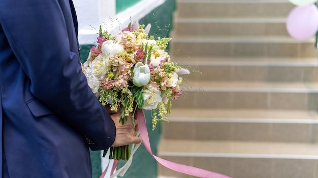 Un novio sosteniendo un ramo exuberante, vista cercana, ceremonia de boda