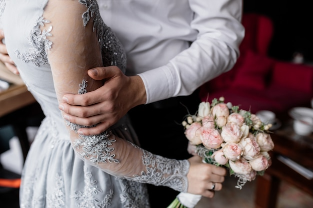 El novio sostiene su amada mano.