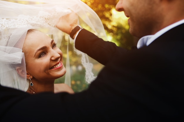 Novio sujetando el velo de la novia