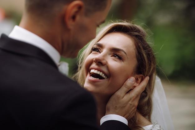 El novio tiene a la novia tierna en sus brazos mientras ella lo mira