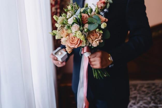 El novio tiene un ramo de novia en sus manos.