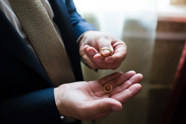 El novio tiene en su mano un anillo de bodas de oro.