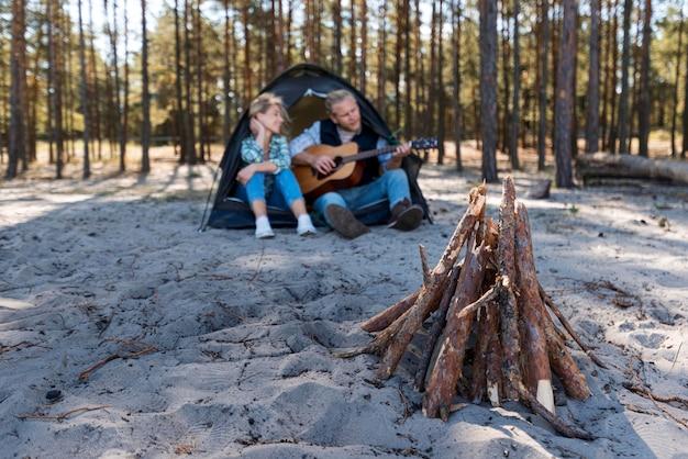 Novio tocando guitarra acústica y madera de fogata
