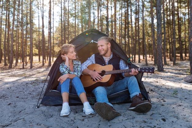 Novio tocando la guitarra acústica en la naturaleza