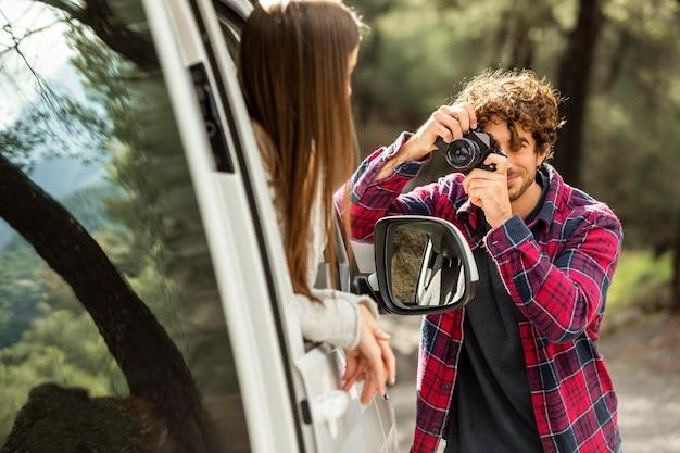 Novio tomando fotografías de novia en el coche durante un viaje por carretera