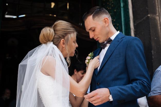 El novio en traje se endereza la corbata bubochku. boutonniere en la solapa de su chaqueta. joven en traje de negocios