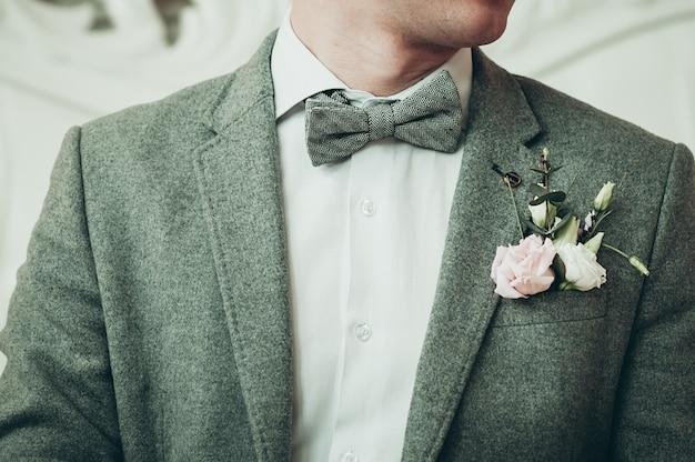 Un novio con traje gris y camisa blanca preparándose para el evento