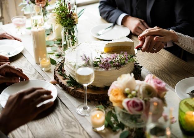 Novio y novia cortando pastel en la recepción nupcial