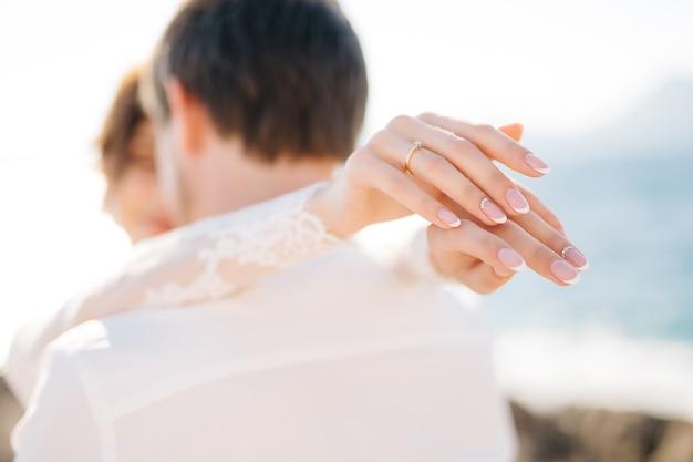 Los novios se abrazan en la playa rocosa de la isla mamula, la novia puso sus manos sobre los hombros del novio