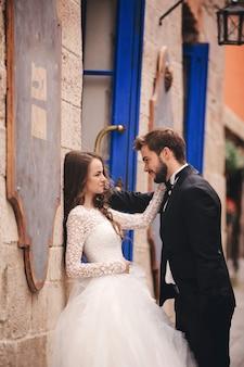Novios abrazándose en la ciudad vieja. puertas y café azul de la vendimia en la ciudad antigua en el fondo. novia elegante en vestido largo blanco y novio en traje y pajarita. día de la boda.