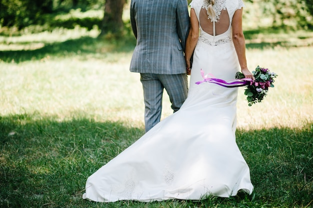 Novios caminando en la naturaleza. la novia con un vestido y el novio van en un jardín verde, campo y sosteniendo un ramo de flores y vegetación. vista trasera.