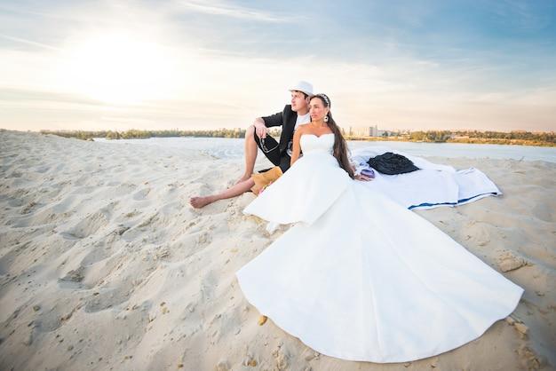 Novios chica encantadora con un vestido blanco y un hombre positivo con sombrero están sentados en la arena blanca de la playa en el fondo