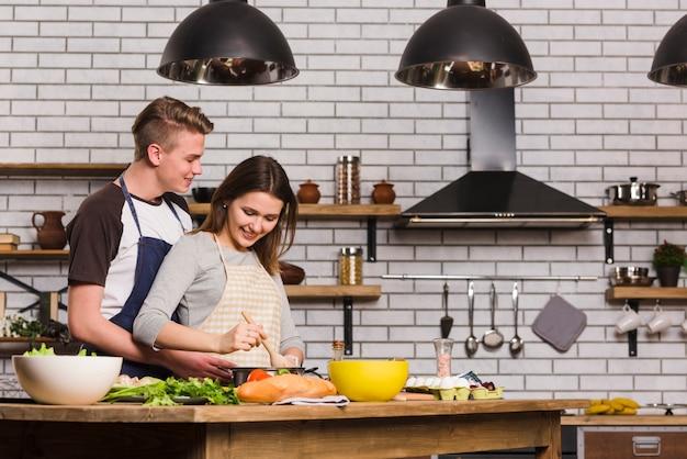 Novios cocinando en la mesa en la cocina