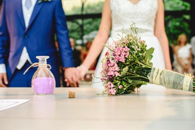 Novios en el día de su boda tomados de la mano románticamente.