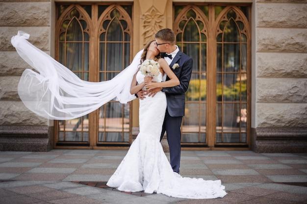 Novios elegantes van a besar a la encantadora novia en la escena de las puertas de madera