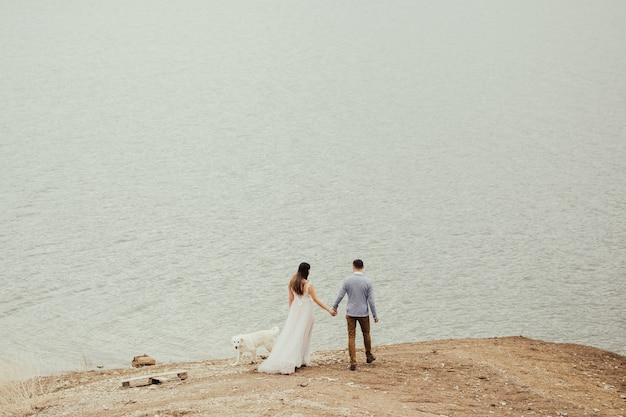 Novios enamorados caminan cerca del lago con un perro blanco.