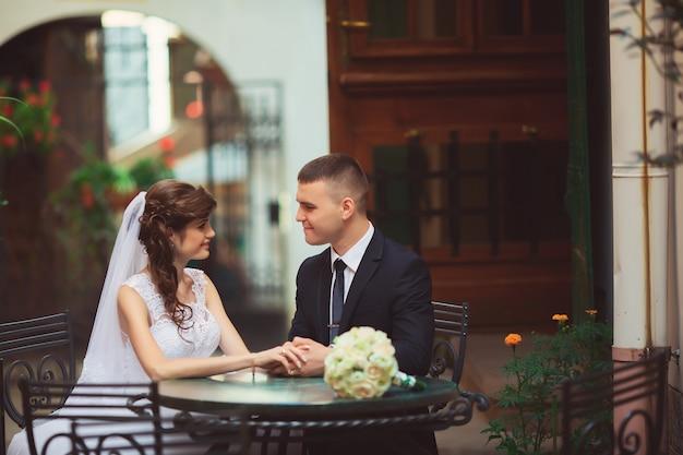 Novios enamorados hermosa novia en vestido blanco y velo y ramo de novias con novio guapo en traje azul sentado en la cafetería. retrato de cuerpo entero de hombre y niña. concepto de boda