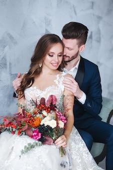 Los novios en el interior se abrazan. mujer hermosa modelo en vestido blanco. hombre de traje belleza novia con novio