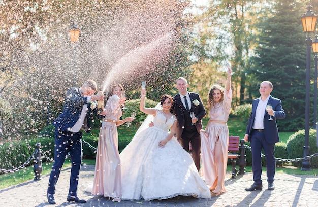 Novios y mejores amigos beben champaña y celebran en el parque el día de la boda