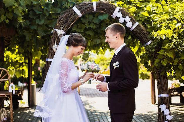 Novios en la naturaleza con la luz solar. amor entre un hombre y una mujer. novia en vestido de novia. el novio en traje. hermoso ramo de novia. verano natural.