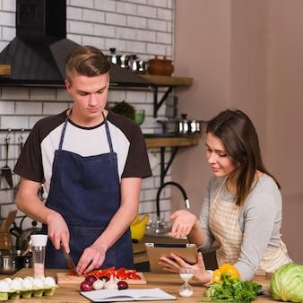 Los novios que cocinan alimentos utilizando tabletas