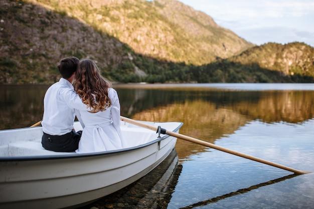 Novios sentados abrazando en un bote en el lago