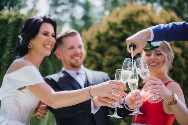 Los novios sonrientes con los mejores amigos beben champán al aire libre y sonríen