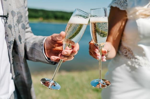 Los novios sostienen una copa de champán y se paran en la naturaleza en la ceremonia de la boda. de cerca. fiesta. mira las gafas. tostado.