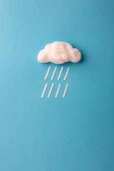 Nube de algodón y gotas de lluvia en azul cielo