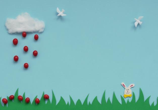 Nube de algodón con la lluvia de pequeños huevos de pascua rojos cayendo sobre la hierba verde, conejito de pascua y palomas blancas sobre azul