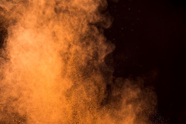 Nube naranja de polvo de maquillaje sobre fondo oscuro