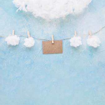 Nubes blancas y tarjeta marrón cuelgan de una cuerda con pinzas para la ropa