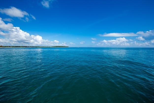 Nubes en el cielo azul sobre el mar en calma con la reflexión de la luz del sol
