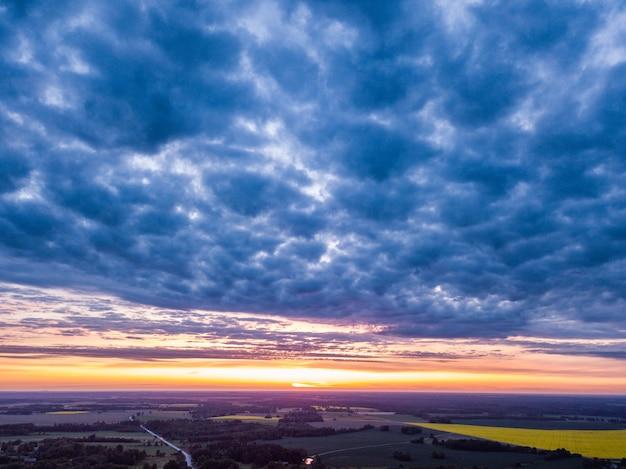 Nubes dramáticas sobre campos de campo con puesta de sol en segundo plano.