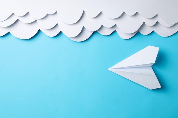 Nubes de papel y plano sobre superficie azul