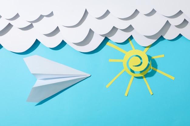 Nubes de papel, sol y avión sobre superficie azul. viaje