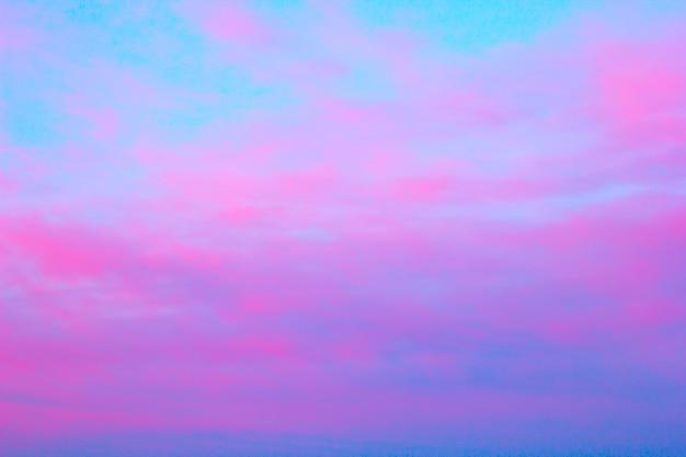 Nubes rosadas brillantes en un cielo azul en la puesta del sol