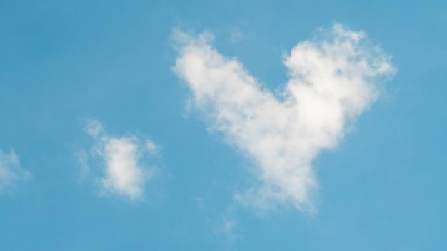 Núblese en una forma del corazón en un fondo azul.
