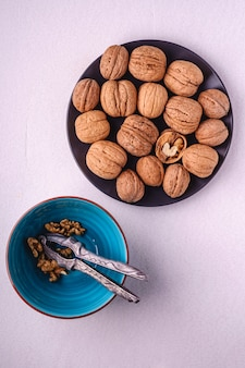 Las nueces apilan la comida con la mitad de la nuez pelada en la placa negra cerca del cascanueces vintage y el tazón azul sobre fondo blanco, vista superior, concepto de comida saludable