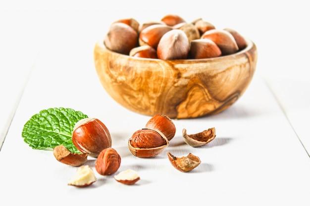 Nueces de la avellana en un cuenco de madera en una tabla de madera blanca. superalimento