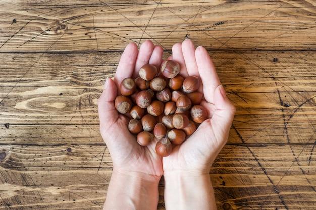 Nueces de avellanas en las palmas de tus manos sobre una oscura superficie de madera vintage.