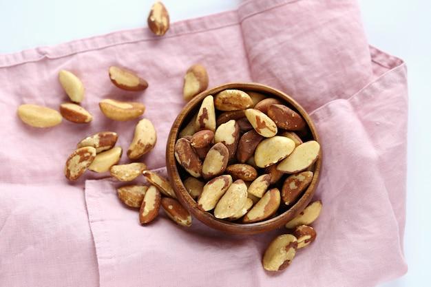 Nueces de brasil en un tazón de madera sobre una servilleta de lino rosa