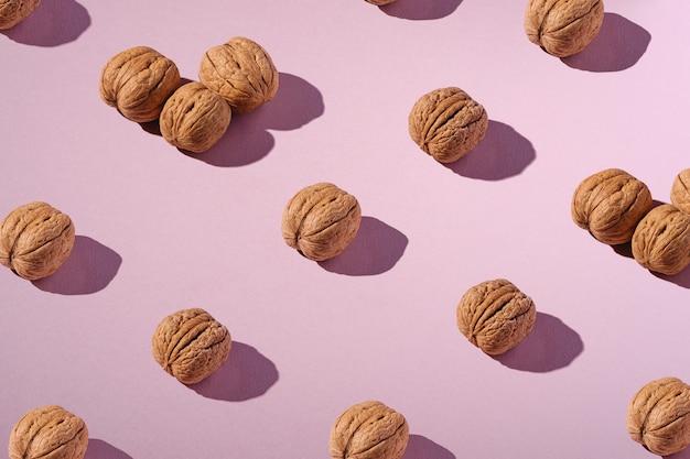Nueces con cáscara en composición de fila, patrón de diseño abstracto minimalista, comida sana, ángulo de visión, fondo rosa