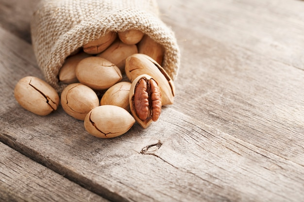 Las nueces se derraman de una tela de saco sobre una mesa de madera