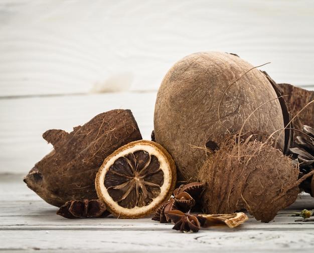 Nueces enteras de coco virutas dispersas de sobre fondo de madera